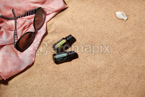 doTERRA Bergamot and Balance with sunglasses and a pink silk scarf on the beach.