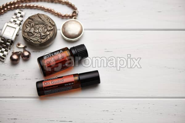 doTERRA On Guard oil and On Guard Touch blend, jewellery and trinkets on white rustic wooden background.