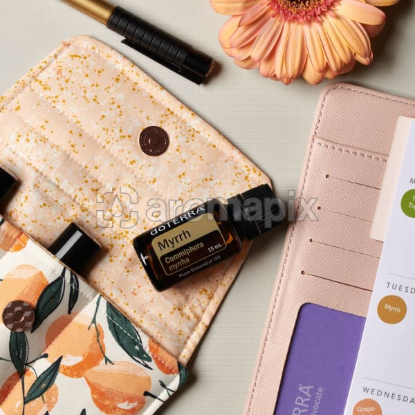 doTERRA Myrrh on an essential oil bag with a flower, pen and diary on a white textured background.