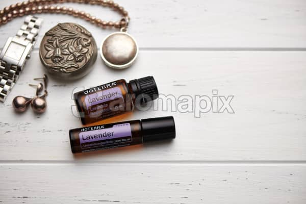 doTERRA Lavender oil and Lavender Touch, jewellery and trinkets on white rustic wooden background.