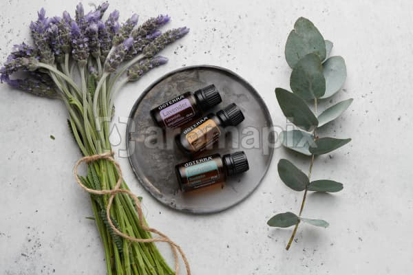 doTERRA Lavender, Tangerine and Eucalyptus on a ceramic plate with lavender stems tied with twine and a eucalyptus stem on a white concrete background.