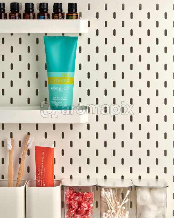 doTERRA Spa Hand and Body on a bathroom shelf with bathroom accessories and additional doTERRA products.