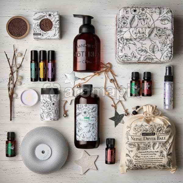 doTERRA 2019 Holiday products including Concrete Lava Rock Diffusers, Holiday Peace Hand Wash and dispenser, Floral Storage Case, Balance Touch, Helichrysum Touch, and Serenity Touch, Holiday Peace, Holiday Joy, Brevi Stone Diffuser, Wintergreen essential oil and Nepal Dryer Balls on a white wooden background.
