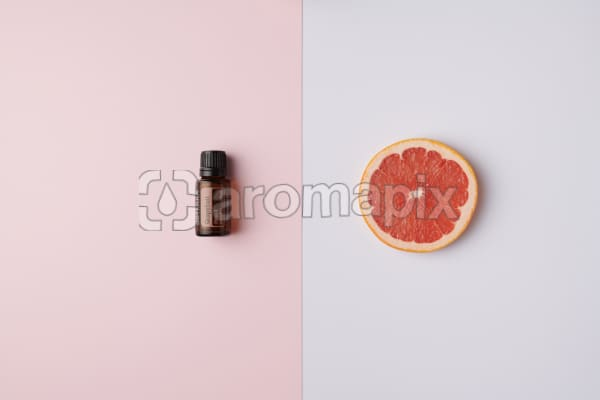doTERRA Grapefruit oil on pink background and grapefruit slice on white background.