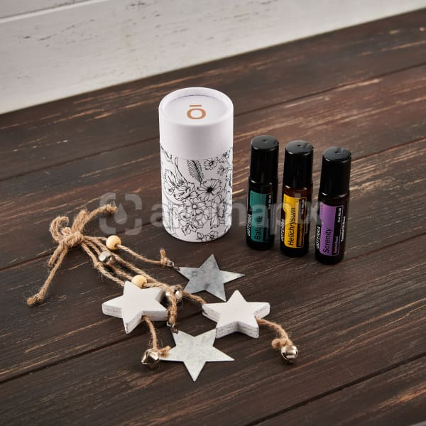 doTERRA Balance Touch, Helichrysum Touch, and Serenity Touch with holiday decorations on a brown wooden background.
