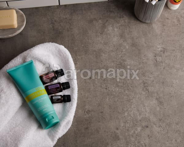 doTERRA Spa Hand and Body Lotion with Geranium, Lavender and Roman Chamomile essential oils and bathroom accessories  on a white towel on a stone background.