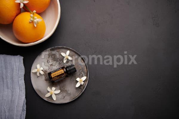 doTERRA Wild Orange with orange blossom flowers on a ceramic plate with a white ceramic bowl filled with seville oranges and orange blossoms on a black concrete background.