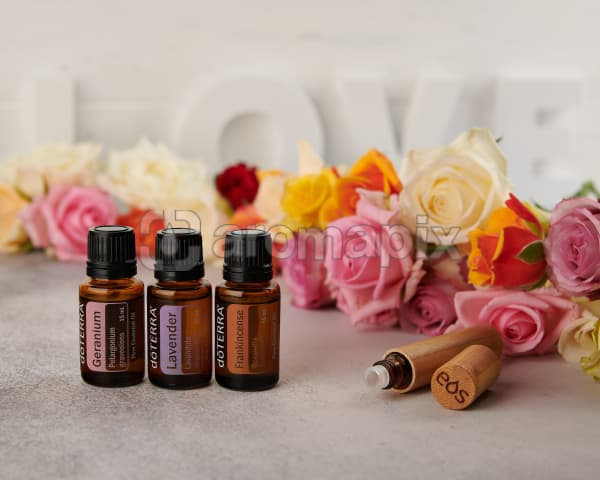 doTERRA Lavender, Frankincense and Geranium with a bamboo roller bottle and roses on a concrete bench top.