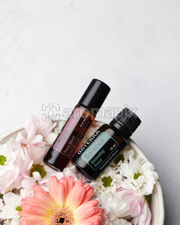 doTERRA InTune 10ml and doTERRA Balance 15ml in a bowl of flowers on a white background.