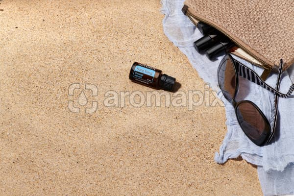 doTERRA Ylang Ylang with sunglasses, scarf and roller bottles in a clutch on the beach.