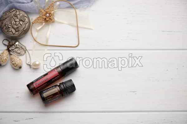 doTERRA Passion Touch and Sandalwood with romantic jewellery on a white vintage wooden background.