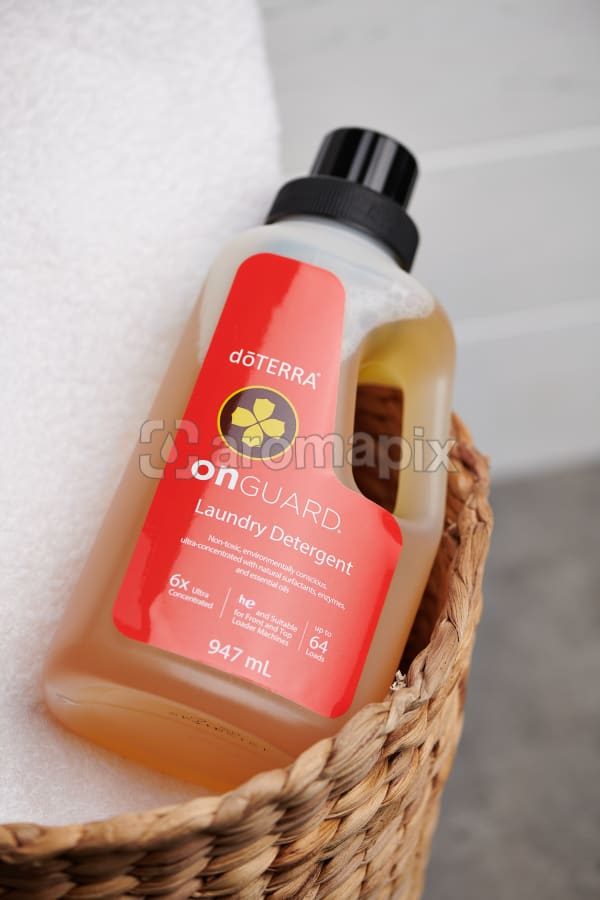 doTERRA On Guard Laundry Detergent on a white towel in a cane basket.