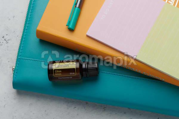 doTERRA Lemon oil with business folder, planner, pen and to do list on white concrete background.