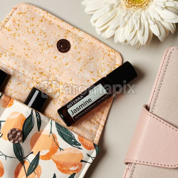 doTERRA Jasmine Touch on an essential oil bag with a white flower and diary on a white textured background.