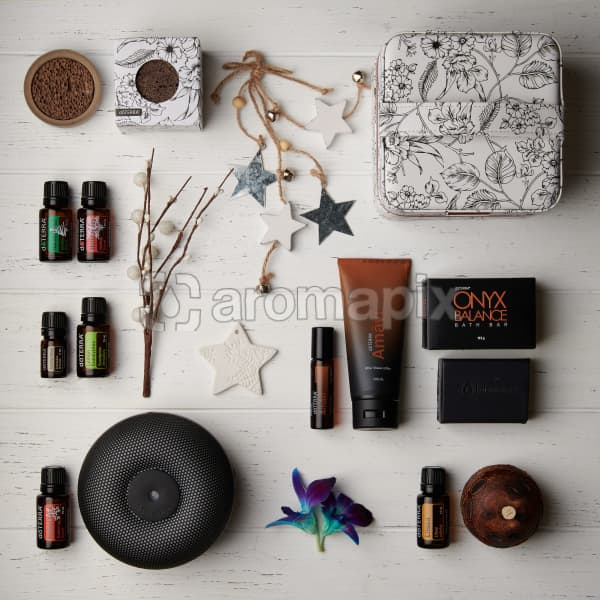 doTERRA 2019 Holiday products including Concrete Lava Rock Diffusers, Floral Storage Case, Holiday Peace, Holiday Joy, Amavi Touch, Amavi After Shave Lotion, Onyx Balance Bath Bar, Buddha Wood, Lemon Eucalyptus, Brevi Walnut Diffuser, Litsea and Aroma Diffuser on a white wooden background.