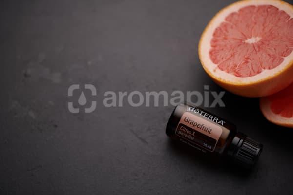 doTERRA Grapefruit oil and grapefruit pieces on black concrete background.