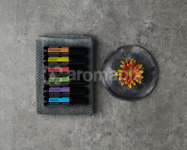 doTERRA Emotional Aromatherapy Touch Kit on a small towel with a flower on gray ceramic plate on a gray stone background.