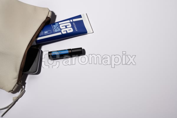 Woman's leather clutch with Ice Blue Rub, Ice Blue Roll On and phone in bright midday sun with a white background.