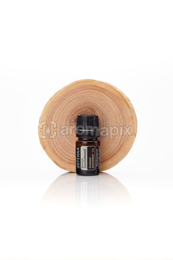 doTERRA Hawaiian Sandalwood with a sandalwood disc on a white background with reflection.