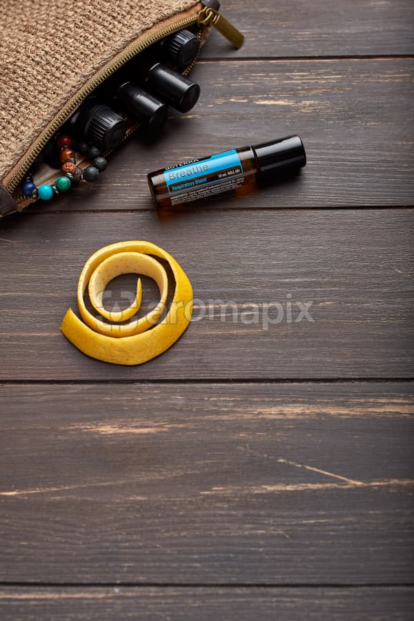 doTERRA Breathe Touch, lemon peel and clutch with oils on brown wooden background.