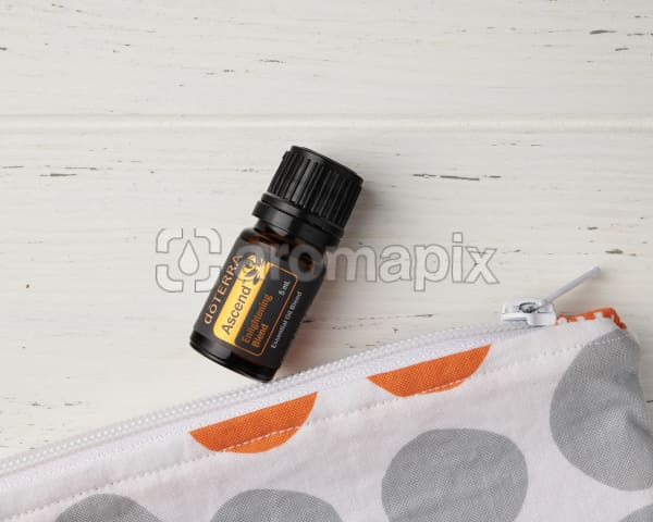 A close up of doTERRA Ascend and the corner of an essential oil bag on a white wooden background.