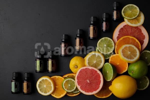 doTERRA citrus oils and slices of citrus fruit on black concrete background.