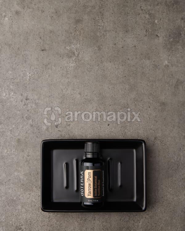 doTERRA Yarrow Pom in a black soap dish on a gray stone background.