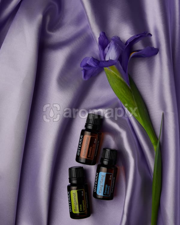 doTERRA Bergamot, Frankincense and Ylang Ylang with a purple flower on pale purple satin.