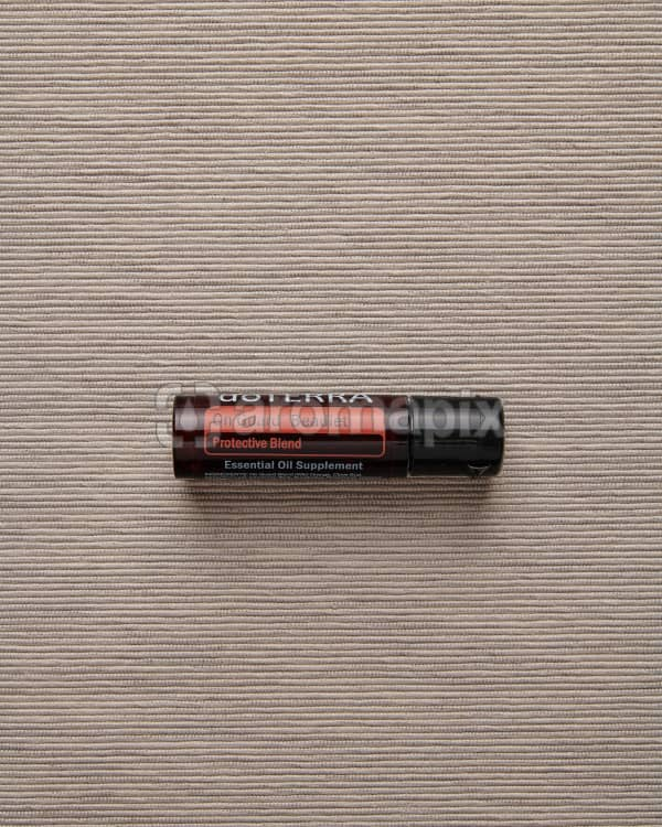 doTERRA On Guard Beadlet on a pale gray textured background.