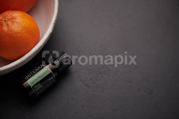 doTERRA Green Mandarin oil and mandarins in white ceramic bowl on black background.