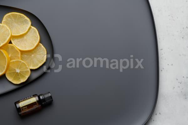 doTERRA Lemon oil and lemon slices on black melamine plate with white concrete background.