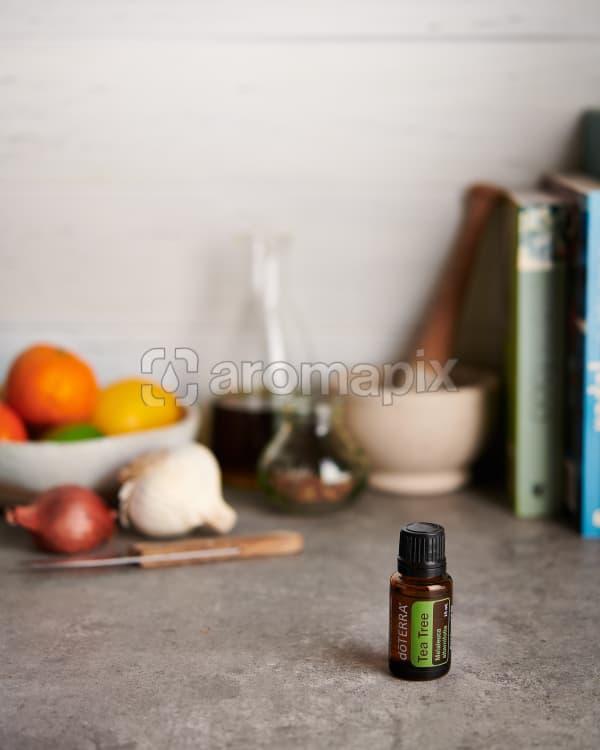doTERRA Tea Tree with kitchen items on a gray stone kitchen bench.