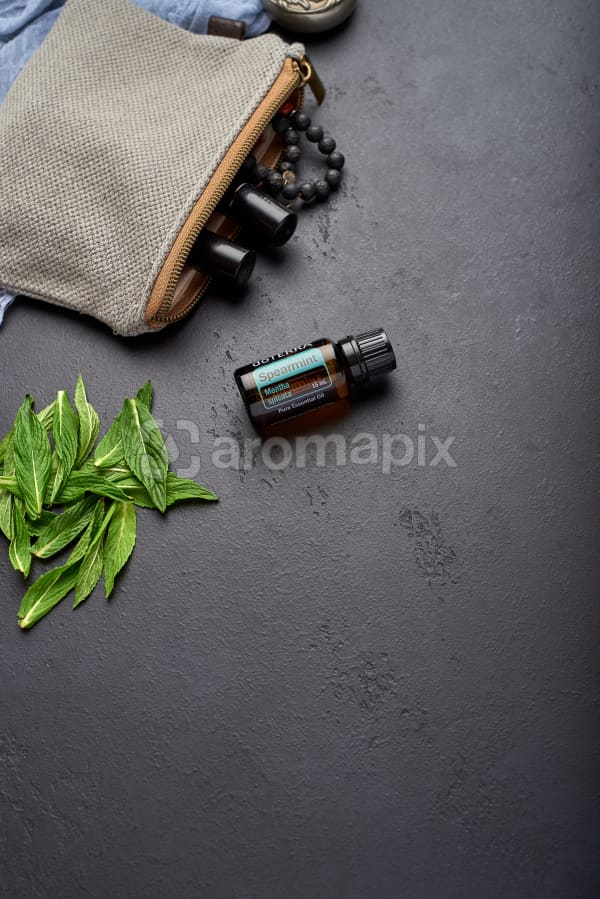 doTERRA Spearmint with clutch, accessories and mint leaves on black concrete background.