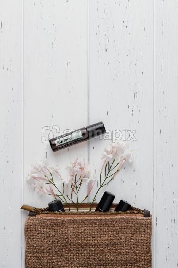 doTERRA Jasmine Touch with jasmine flowers and a clutch filled with roller bottles on a white wooden background.