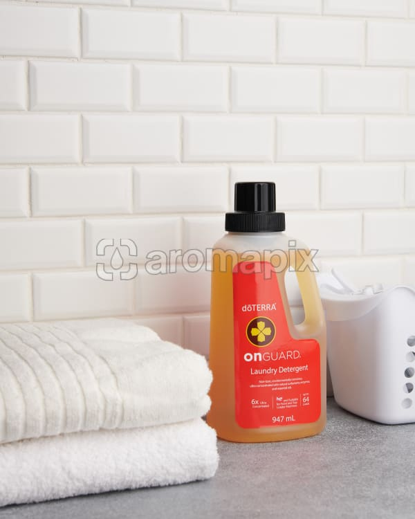 doTERRA On Guard Laundry Detergent and towels on a laundry bench on a white tiled background.
