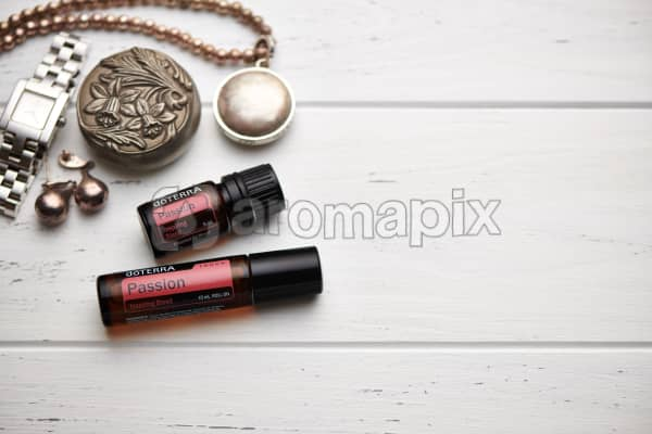 doTERRA Passion oil and Passion Touch blend, jewellery and trinkets on white rustic wooden background.
