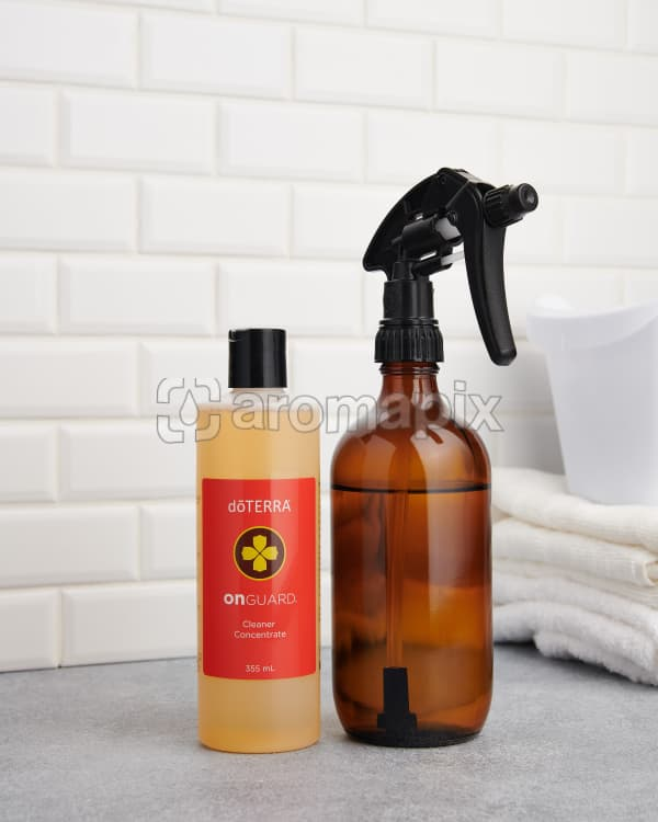 doTERRA On Guard Cleaner Concentrate with an amber spray bottle on a bench top.