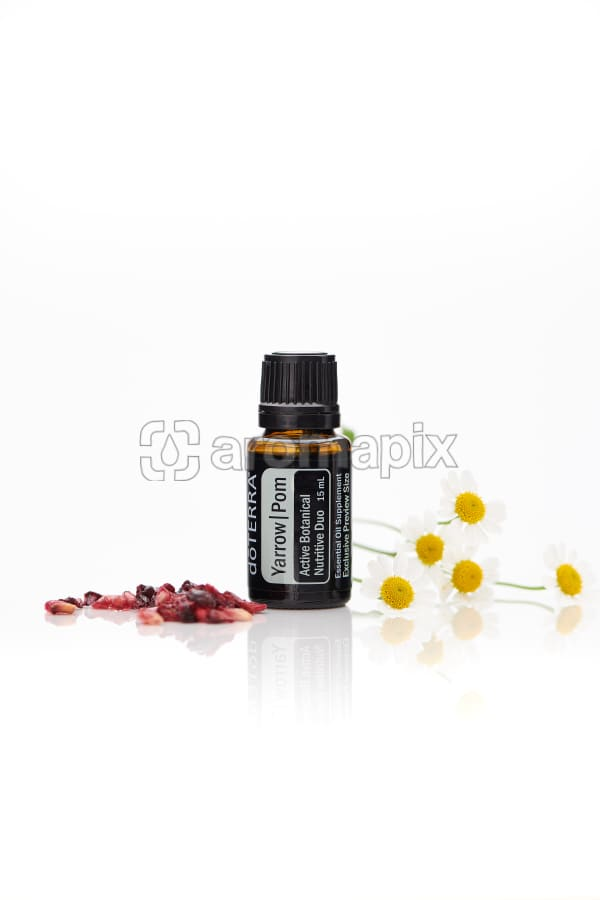 doTERRA Yarrow Pom with pomegranate seeds and flowers on a white background with reflection.