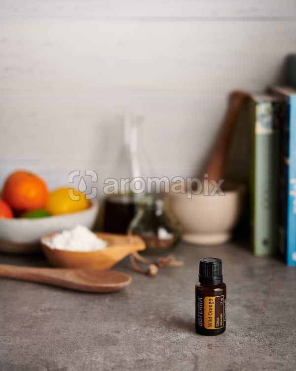 doTERRA Wild Orange  and a bowl of citrus fruit with kitchen equipment on a gray stone kitchen bench.