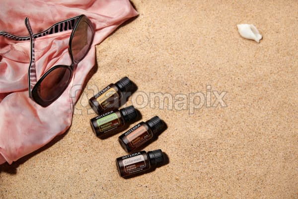 doTERRA Wild Orange, Rosemary, Frankincense and Cedarwood with sunglasses and a pink silk scarf on the beach.