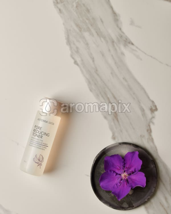 doTERRA Pore Reducing Toner with a purple flower in a gray ceramic plate on a white marble background.