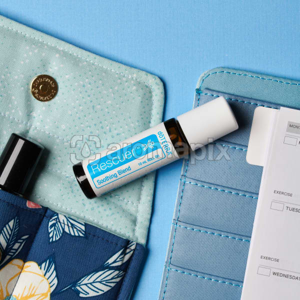 doTERRA Rescuer on an essential oil bag with a diary on a blue textured background.