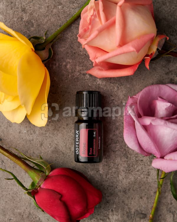 doTERRA Rose essential oil with roses on a gray stone background.