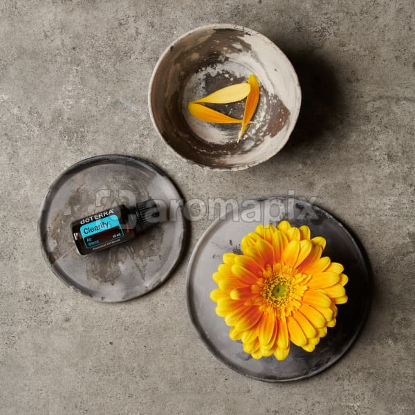 doTERRA Clearify on a ceramic plate, a yellow flower on a ceramic plate and petals in a small ceramic bowl on a grey stone background.