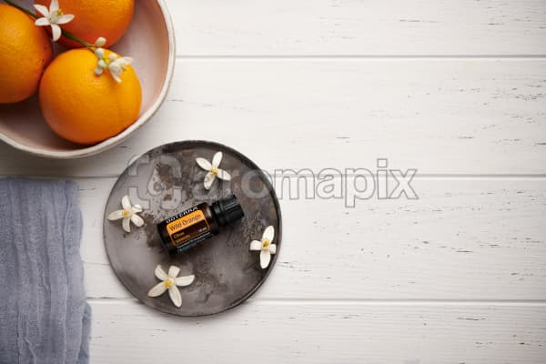 doTERRA Wild Orange with orange blossom flowers on a ceramic plate with a white ceramic bowl filled with seville oranges and orange blossoms on a white wooden background.