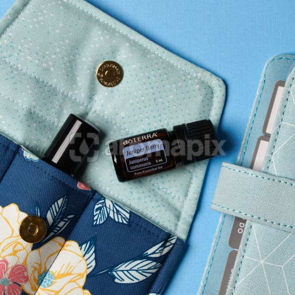 doTERRA Juniper Berry on an essential oil bag with a diary on a blue textured background.