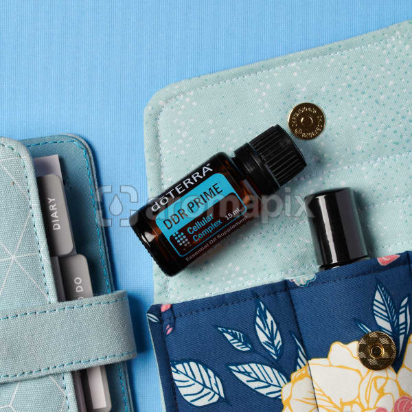 doTERRA DDR Prime on an essential oil bag with a diary on a blue textured background.