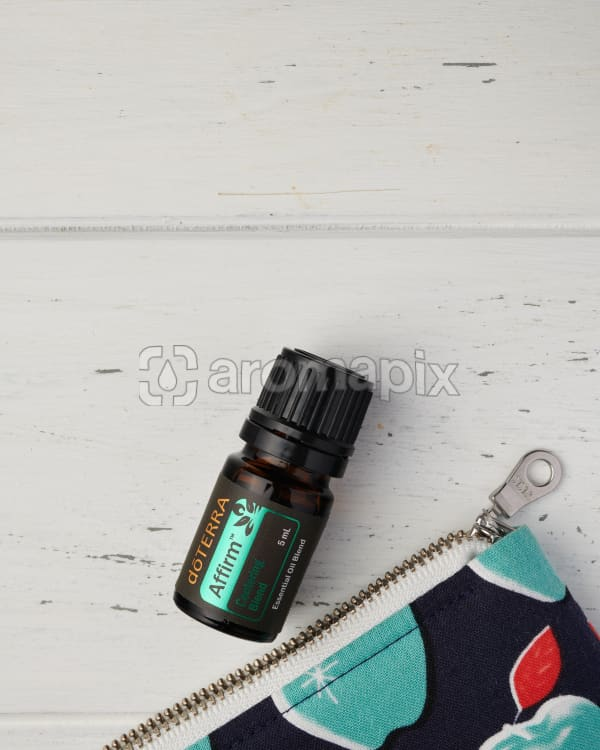 A close up of doTERRA Affirm and the corner of an essential oil bag on a white wooden background.