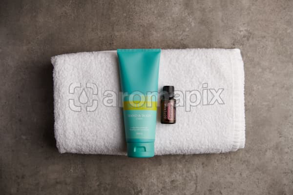 doTERRA Spa Hand and Body Lotion with Geranium essential oil on a white towel on a stone background.