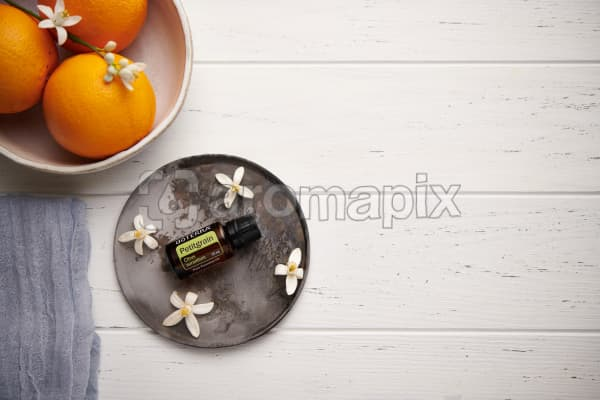 doTERRA Petitgrain with orange blossom flowers on a ceramic plate with a white ceramic bowl filled with seville oranges and orange blossoms on a white wooden background.